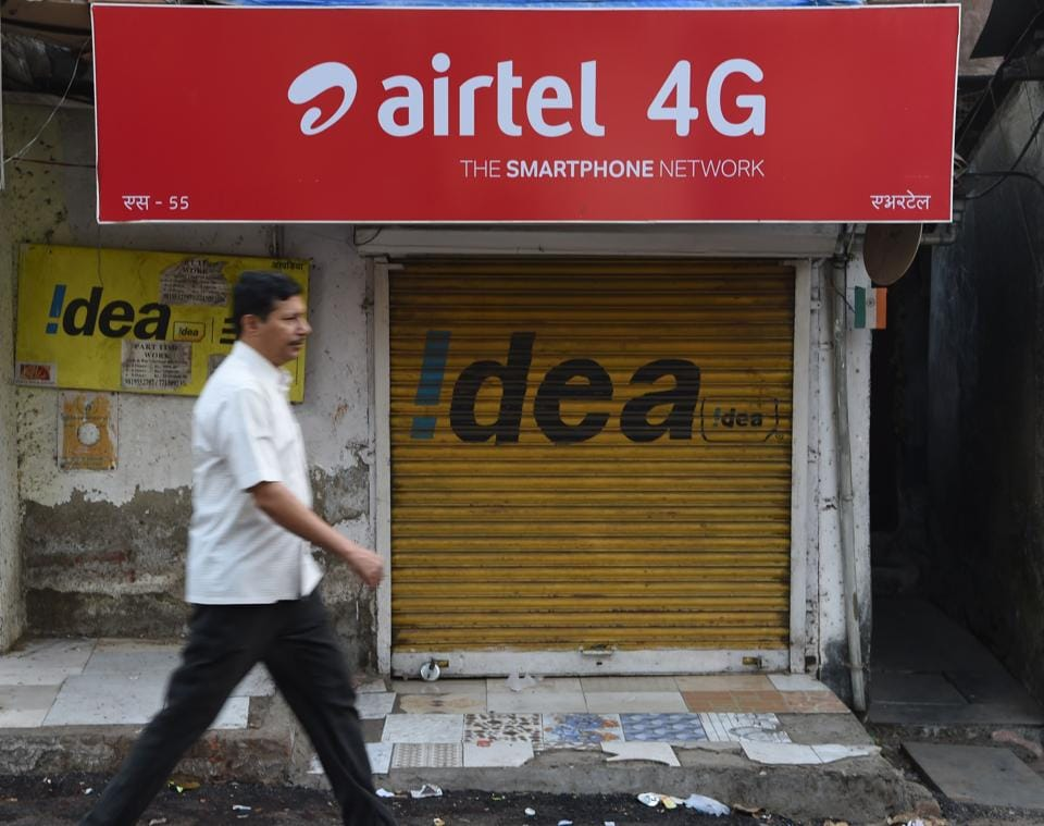 Man walking past a shop with an advertisement for mobile service provider Airtel and Idea in Mumbai. Buyouts, mergers and quick exits -- as India's richest man shakes up the country's ultra-competitive mobile market, telecommunications companies are scrambling to either consolidate or cut their losses and run.