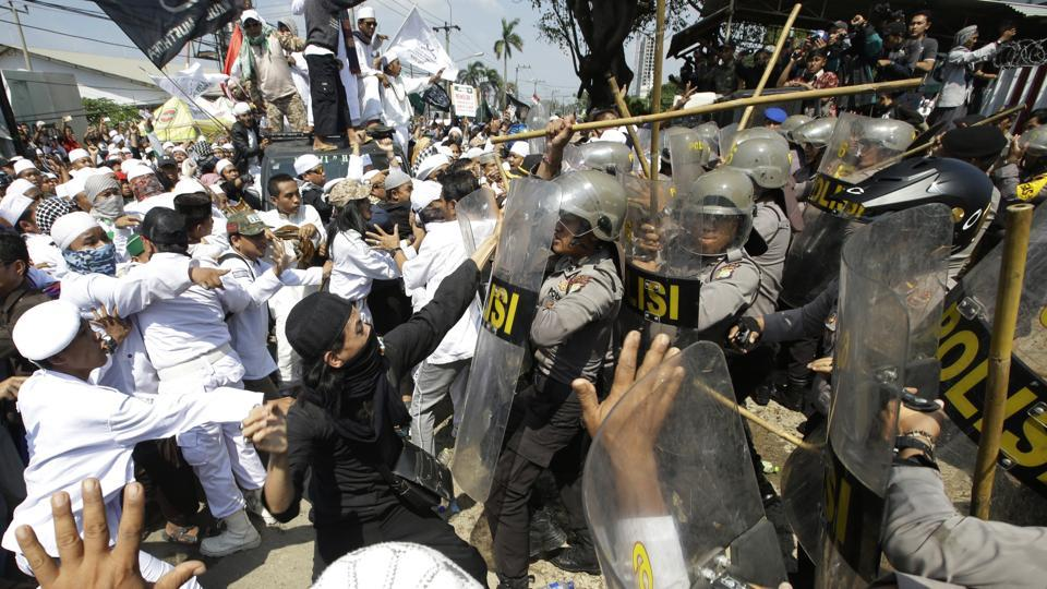 Police officers clash with Muslim hardliners during a protest against the construction of a Catholic church in Bekasi, Indonesia.