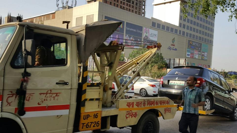 Noida traffic police tow away cars parked illegally outside Logix mall in Noida. The drive has been initiated to decongest city roads.