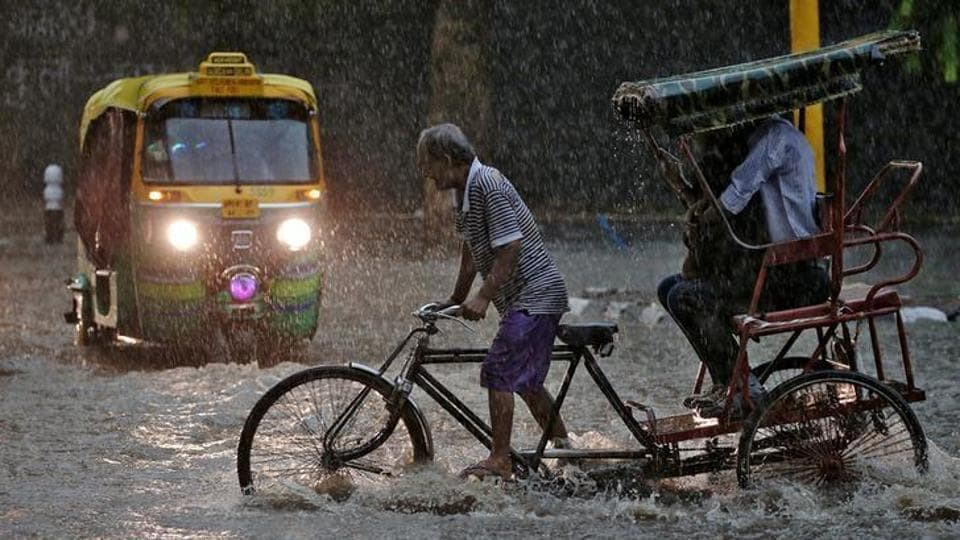 A man pedals his cycle rickshaw during monsoon rains in New Delhi.