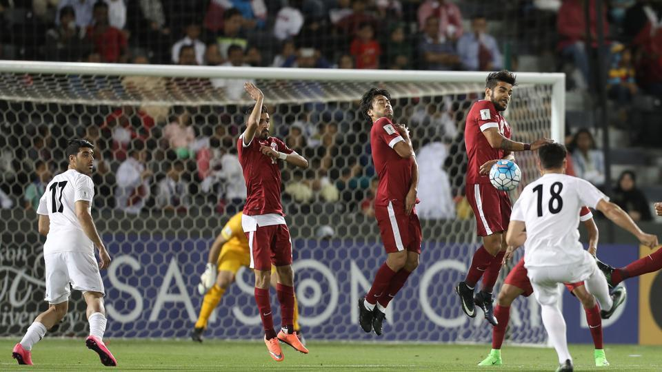 Iran's forward Alireza Jahan Bakhsh (R) takes a free kick against Qatar during a 2018 FIFA World Cup qualifying football match.