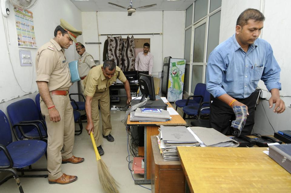 Police personnel clean the office of the superintendent of police in Noida's Sector 6.