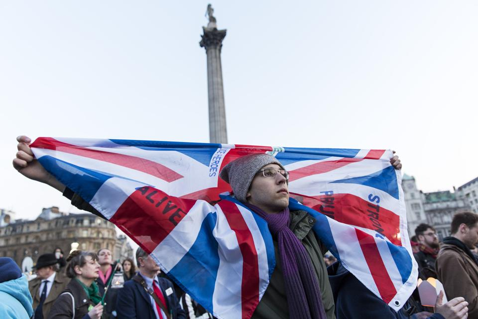 A man holds a Union Jack during a vigil at Trafalgar Square in London.