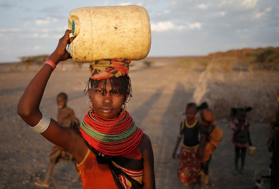 A woman carries a water canister in a village near Loiyangalani. (Goran Tomasevic / Reuters)