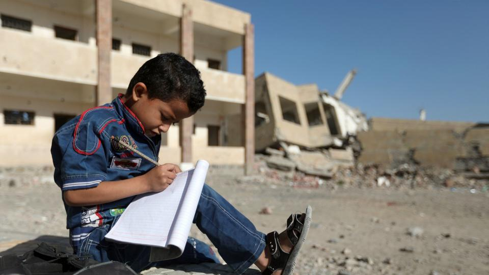 A Yemeni boy school writes as he sits outside a school on March 16, 2017, that was damaged in an air strike in the southern Yemeni city of Taez.