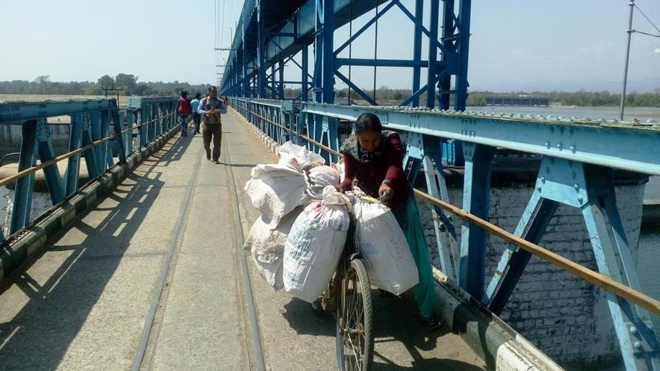 A Nepalese woman pushes her goods laden bicycle on the Sharda barrage at Banbasa.
