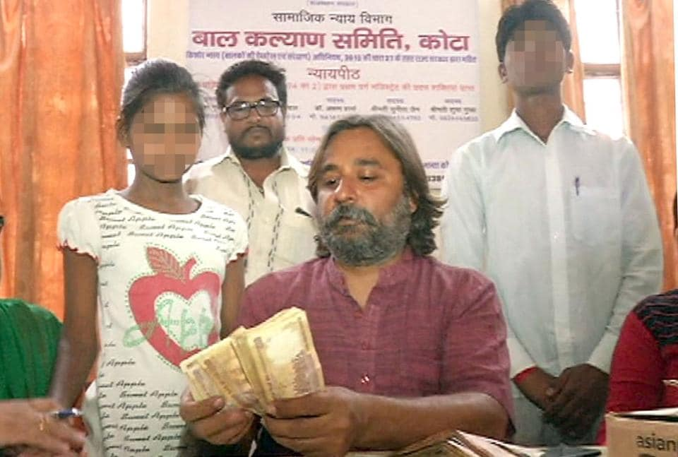 Child Welfare Committee chairman Harish Gurubakshani holds the bundle of banned notes with the two kids (faces blurred) by his side in Kota.