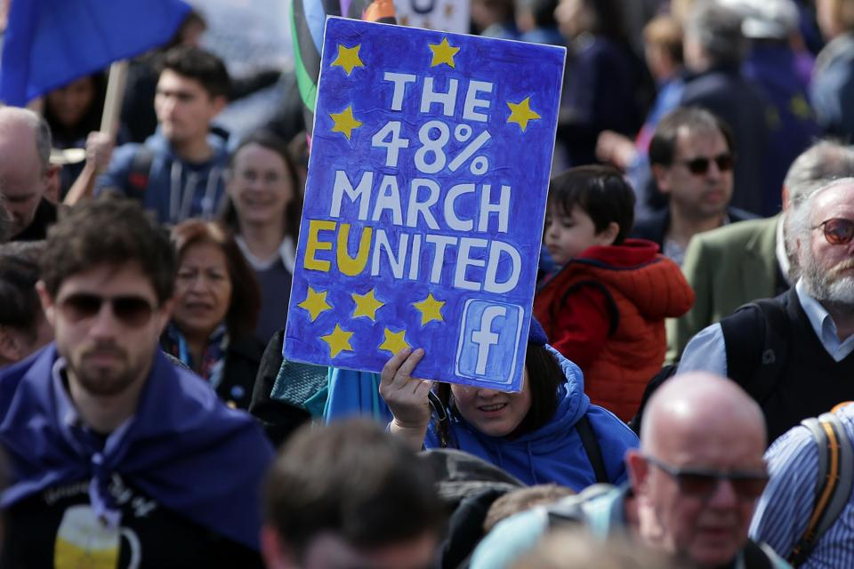 Demonstrators hold placards and wave EU flags as they participate in an anti Brexit, pro-EU march in London.