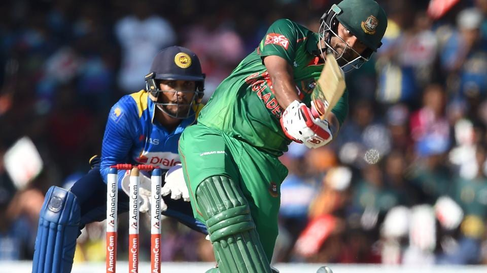 Bangladesh cricketer Tamim Iqbal (R) plays a shot as Sri Lankan wicketkeeper Dinesh Chandimal (L) looks on during the first one day international (ODI) cricket match between Sri Lanka and Bangladesh at The Rangiri Dambulla International Cricket Stadium in Dambulla on Saturday. Get highlights of Sri Lanka vs Bangladesh here.