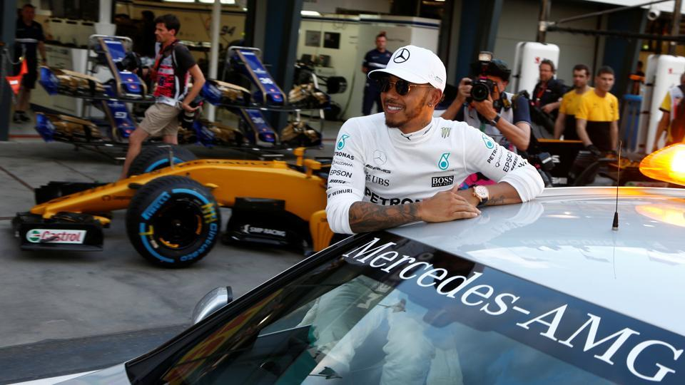 Lewis Hamilton rides in a car down pit lane after qualifying fastest for Formula One's Australian Grand Prix.