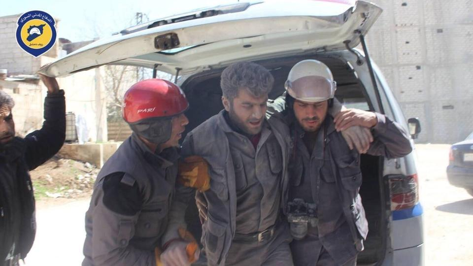 In this photo provided by the Syrian Civil Defense group known as the White Helmets, Civil Defense workers help their teammate after airstrikes hit a main street, killing many people, activists said, in the Damascus suburb of Hamouriyeh, Syria on March 25.