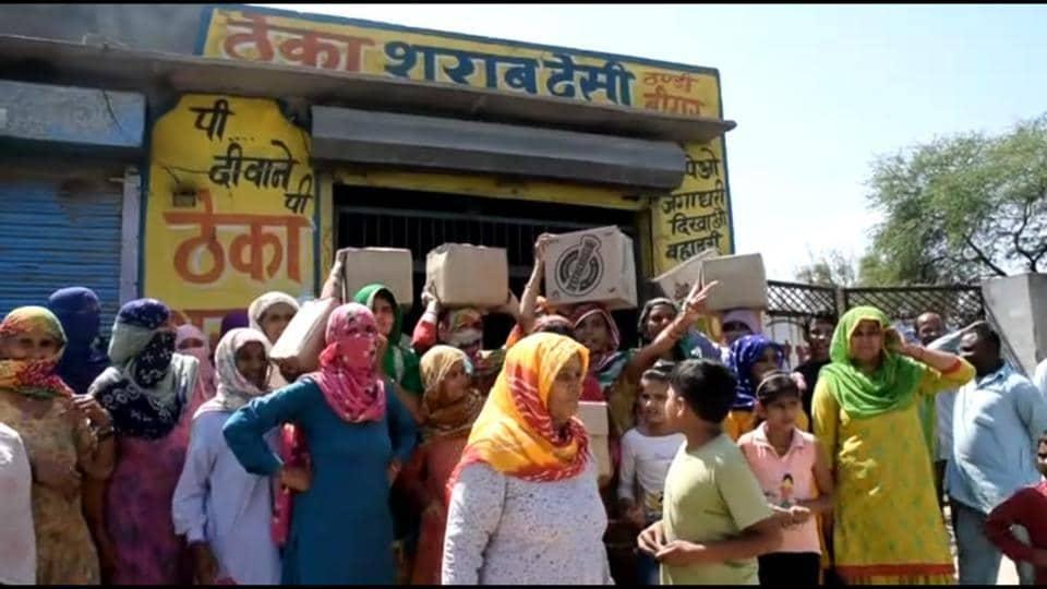 Women outside a liquor vend at Gamri village in Sonepat.