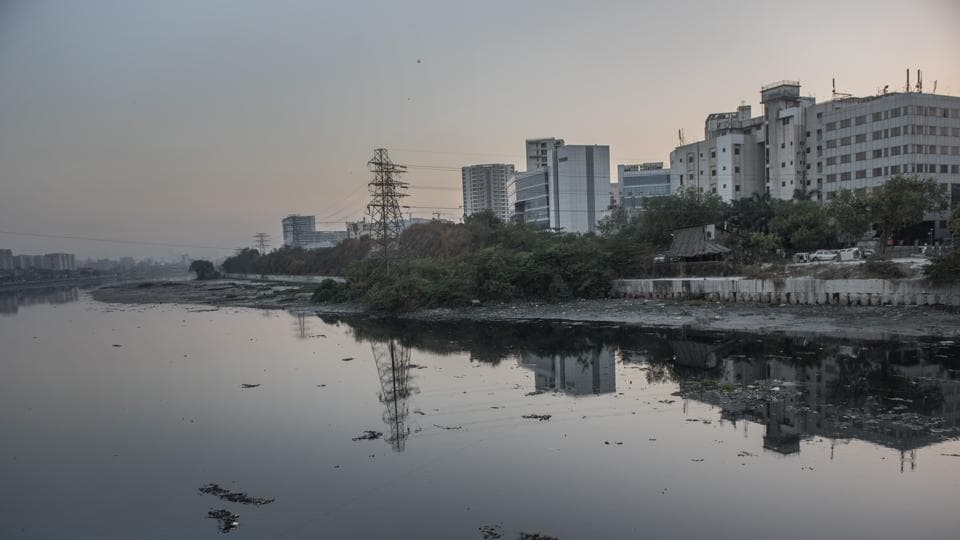 The Mithi flows dark and turgid by the swanky high-rises of the Bandra-Kurla Complex.  (Satish Bate/HT Photo)