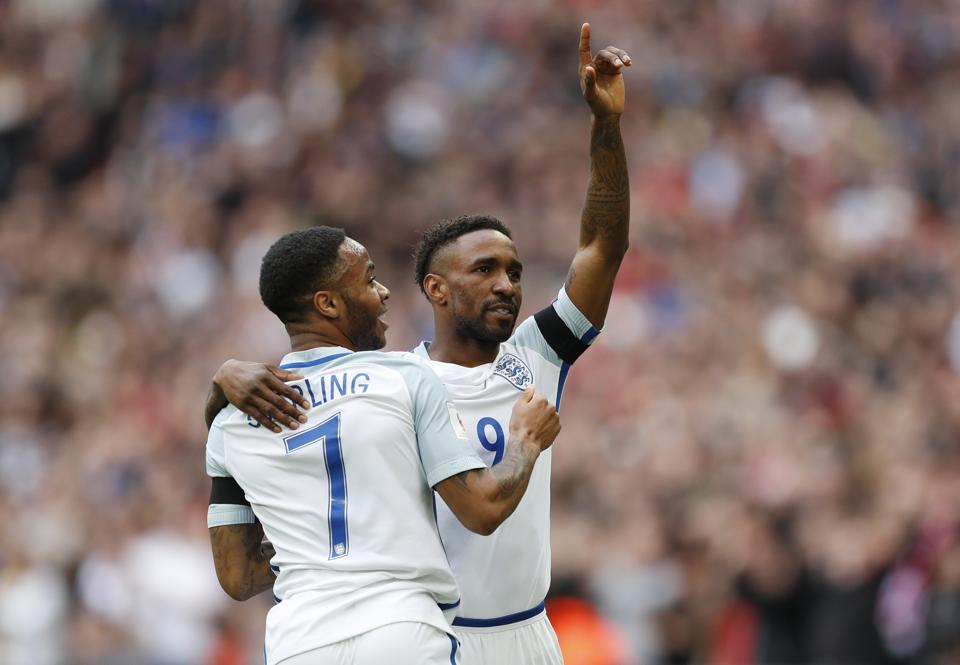 England's Jermain Defoe celebrates scoring their first goal against Lithuania on Sunday with teammate Raheem Sterling.