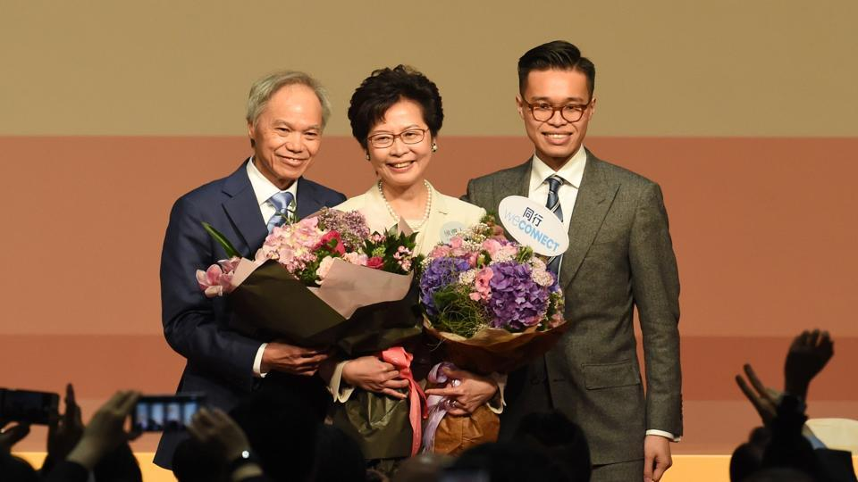 Carrie Lam (centre) holds bouquets as she stands on stage after winning the Hong Kong chief executive election on Sunday.