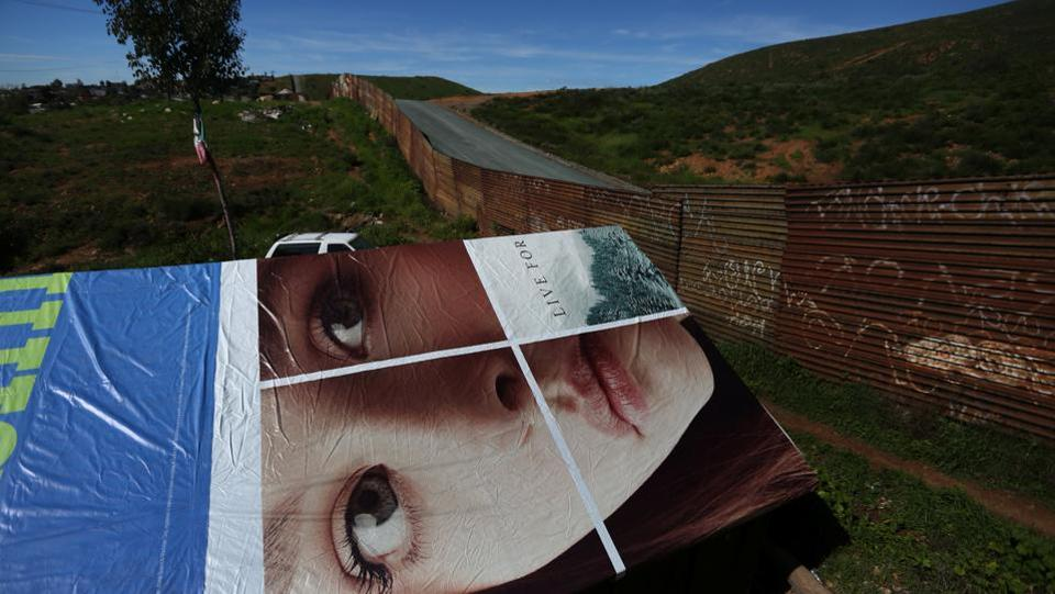 The roof of a house made with an advertisement banner is seen next to a section of the border fence separating Mexico and the United States, on the outskirts of Tijuana, Mexico. (Edgard Garrido/REUTERS)