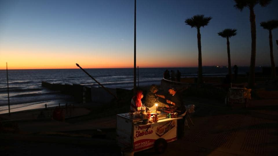 A man sells hot dogs next to the fence separating Mexico and the United States, in Tijuana, Mexico. (Edgard Garrido/REUTERS)