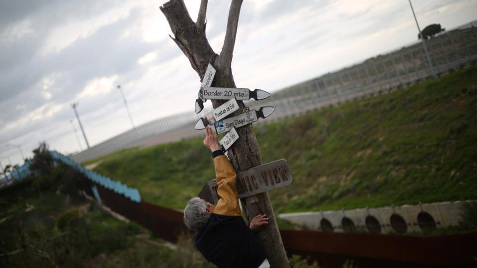 Mexican architect Carlos Torres, 68, adjusts signs near the double border fences separating Mexico and the United States. (Edgard Garrido/REUTERS)