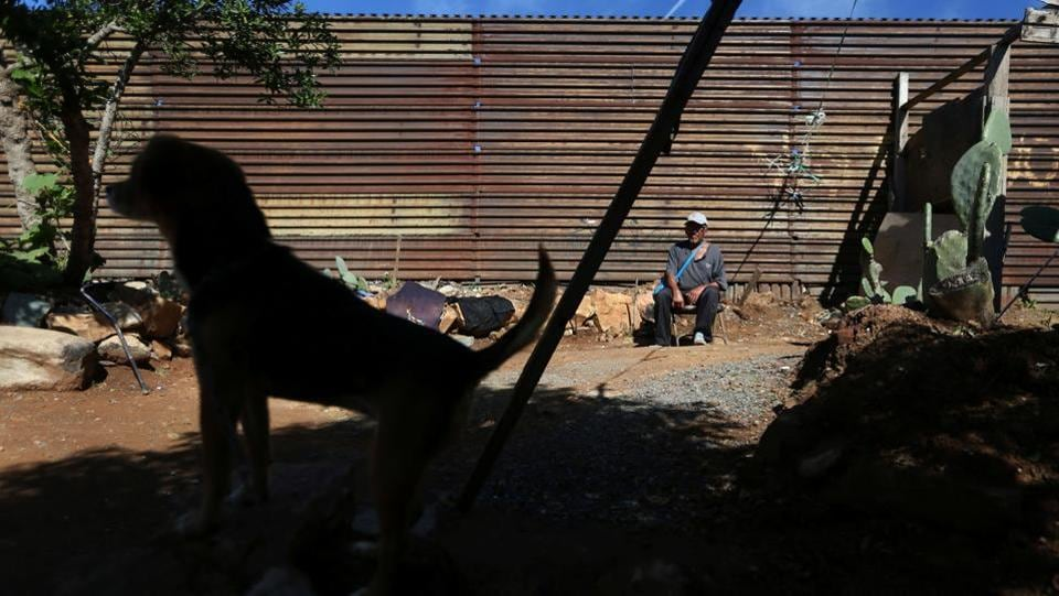 Pensioner Pedro, 72, rests outside his home near a section of the fence separating Mexico and the United States, on the outskirts of Tijuana, Mexico. Neither Trump nor the wall is going to stop anyone, maybe just for a moment, he said. (Edgard Garrido/REUTERS)