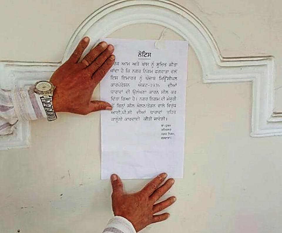 MC officials pasting notice after locking a property.