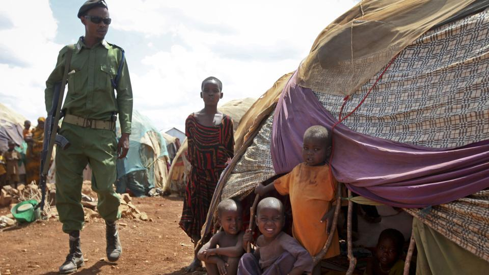 A Somali policeman walks past as newly displaced Somali children stand outside their makeshift shelter at a camp in Baidoa. (Farah Abdi Warsameh/AP)