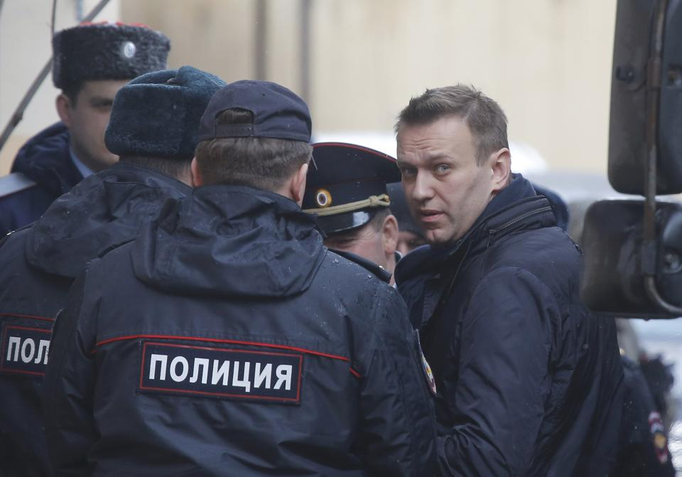 Russian opposition leader Alexei Navalny is escorted upon his arrival for a hearing in Moscow after being detained at a protest against corruption and demanding the resignation of Prime Minister Dmitry Medvedev.