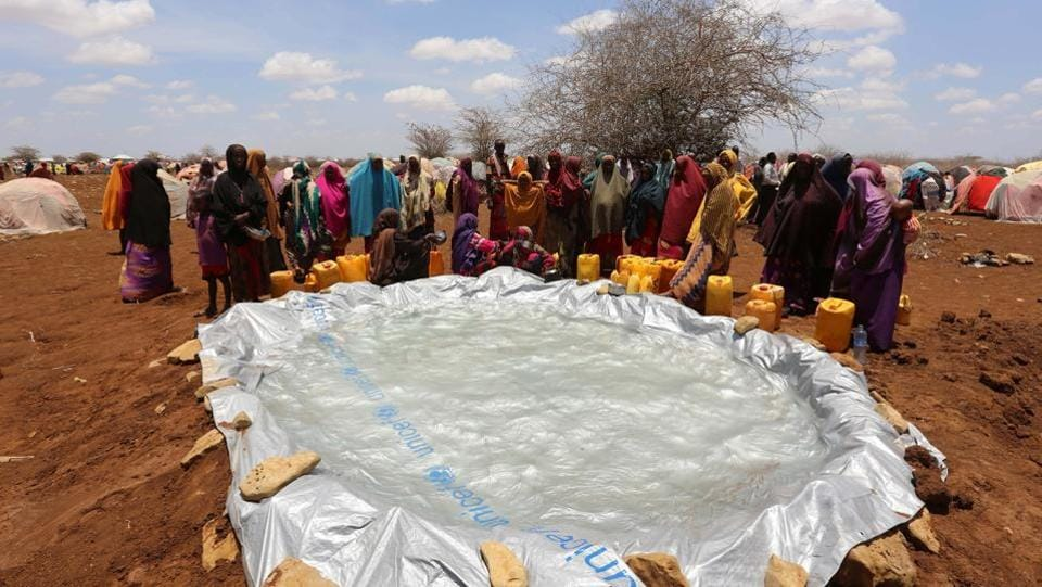 Internally displaced Somali women gather to collect water from a plastic pan near a makeshift camp in Baidoa. Water scarcity also remains a major problem among the new arrivals in the refugee camps. (Feisal Omar/REUTERS)