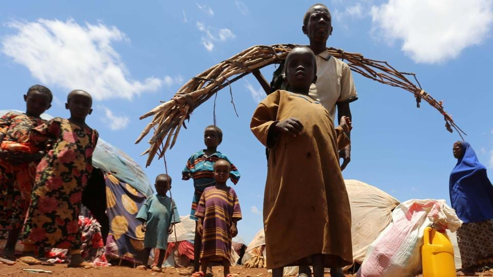 Internally displaced Somali people are seen outside their shelter after fleeing from drought stricken regions at a makeshift camp in Baidoa.  The hospital ward is filled with the sound of crying, malnourished children, many fed through tubes in their noses. (Feisal Omar/REUTERS)