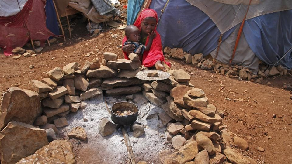A newly displaced Somali girl holds her sister as they cook food over a fire, next to their makeshift shelter at a camp in Baidoa, Somalia.  (Farah Abdi Warsameh/AP)