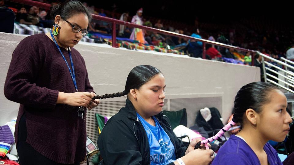 Sunshine Hayes (L) braids her sister Skye's hair, while Skye does the same for Ariana Hollow Horn, prior to the start of the 43rd Annual Denver March Powwow. (Jason Connolly / AFP)