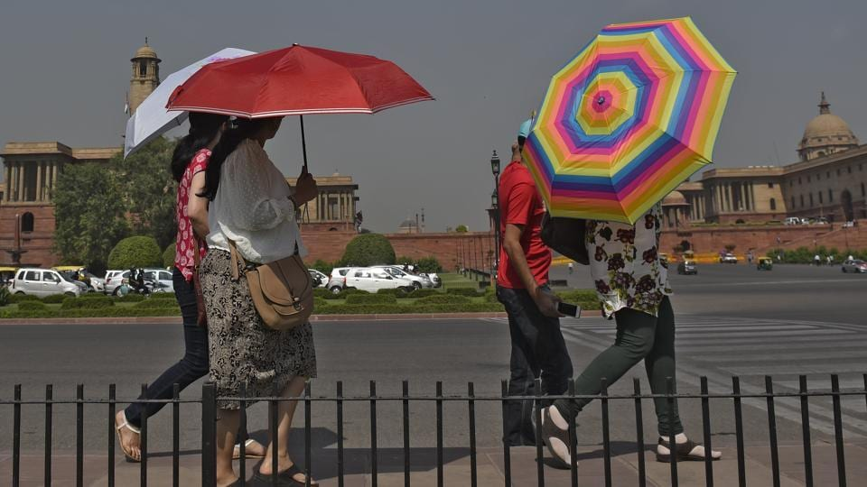 Women use umbrellas to protect themselves from the heat in New Delhi.
