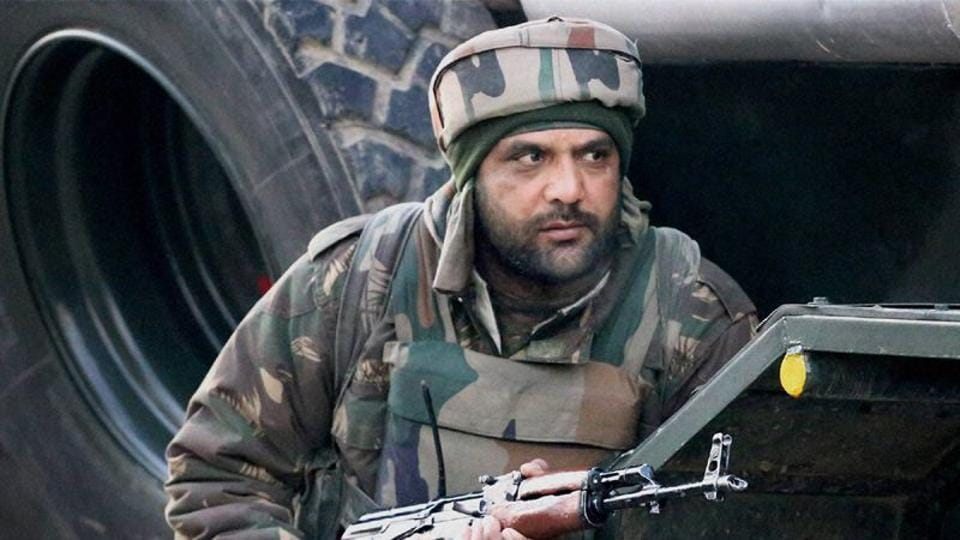 A soldier takes position during an encounter with militants in north Kashmir's Sopore town.