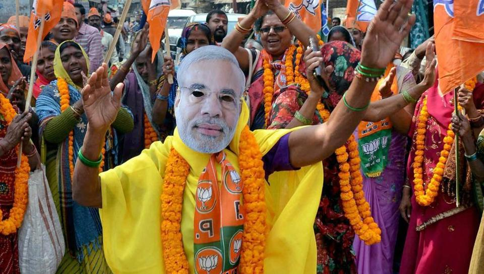 A woman supporter of BJP dances while wearing a mask of Prime Minister Narendra Modi at an election campaign in Mirzapur.