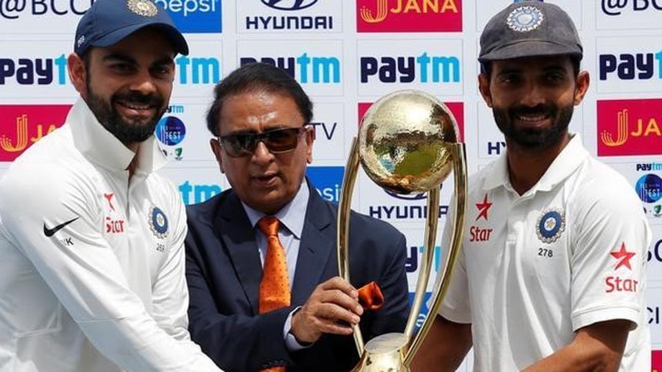 India's Virat Kohli (L) and Ajinkya Rahane (R) receive the Border-Gavaskar trophy after beating Australia in Dharamsala.