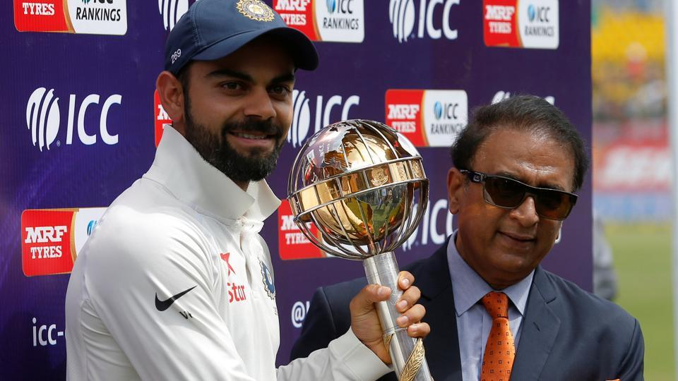 Virat Kohli receives the ICC Test Championship Mace from Sunil Gavaskar after their series win over Australia.