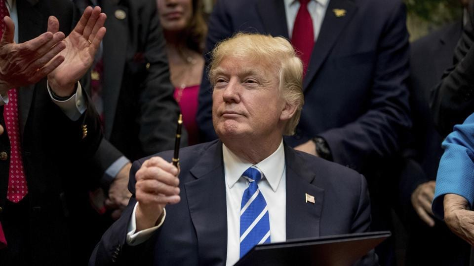 In this March 27 photo, President Donald Trump holds up a pen he used to sign one of various bills in the Roosevelt Room of the White House in Washington.