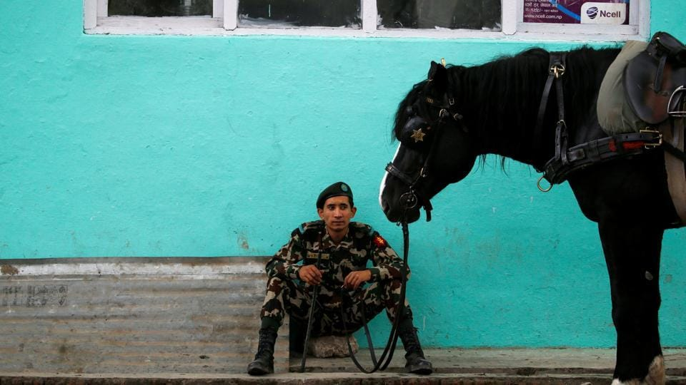 Nepal army soldier sit next to a horse during the religious Ghode Jatra festival, organised by the Nepal army. (Navesh Chitrakar/REUTERS)