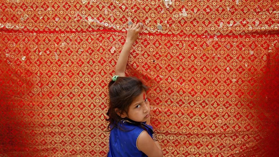 A girl looks on as she sticks a coin on the wall of a temple  on the first day  of Navratri festival  in Jammu. (Mukesh Gupta / REUTERS)