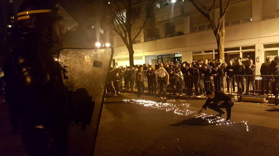 Youths use candles to write the word 'violence' in the road in front of a line of riot police outside the commisariat of the 19th district of Paris on Monday night.