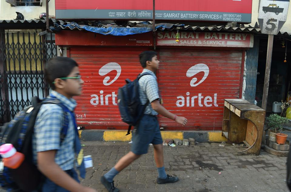Indian students walking past a shop with an advertisement for mobile service provider Airtel in Mumbai. Buyouts, mergers and quick exits -- as India's richest man shakes up the country's ultra-competitive mobile market, telecommunications companies are scrambling to either consolidate or cut their losses and run.