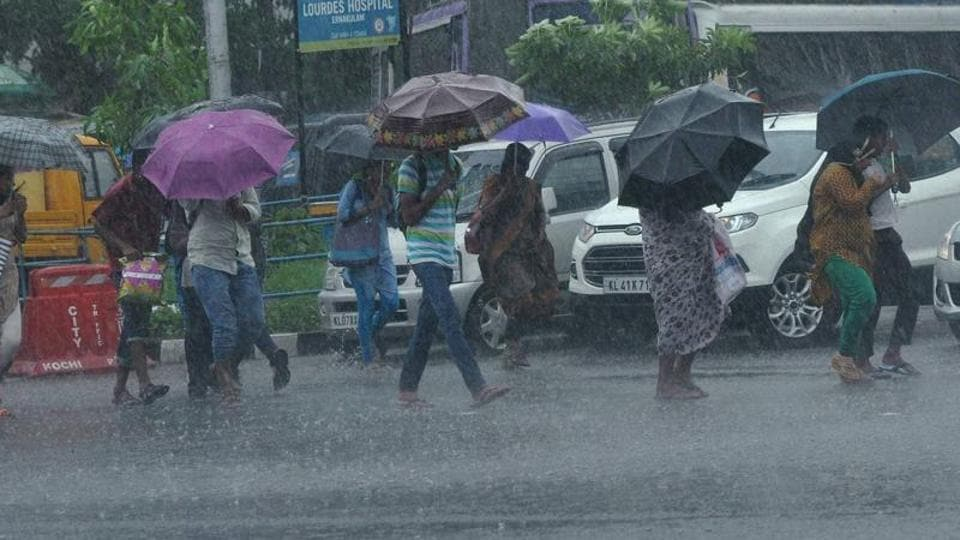 People, holding umbrellas, walk at a road during the first monsoon rains in southern India.