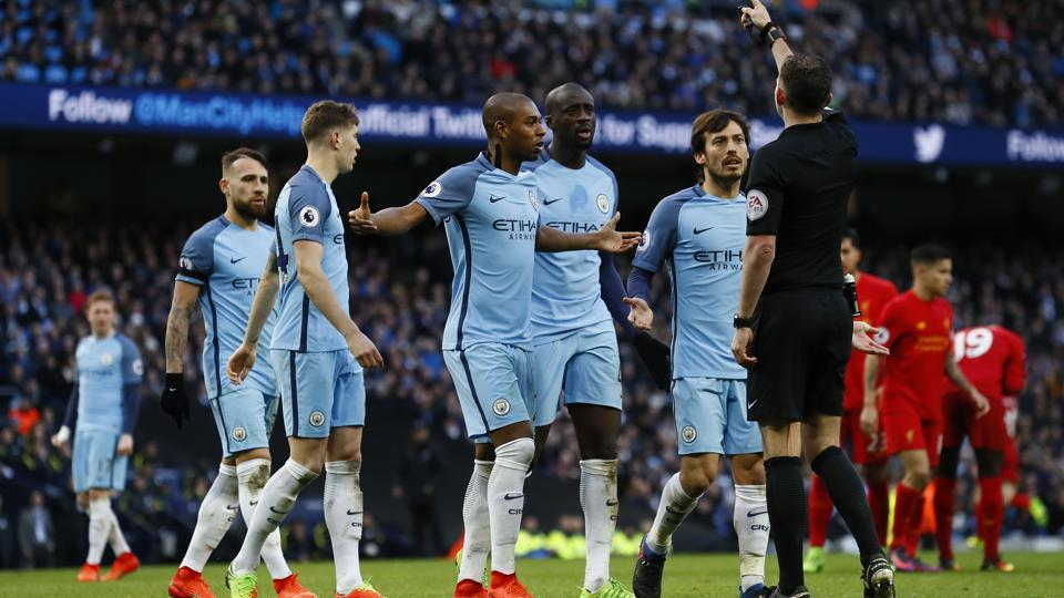 Referee Michael Oliver speaks to Manchester City's David Silva (R) and team mates after awarding Liverpool a penalty during their Premier League clash on March 20.
