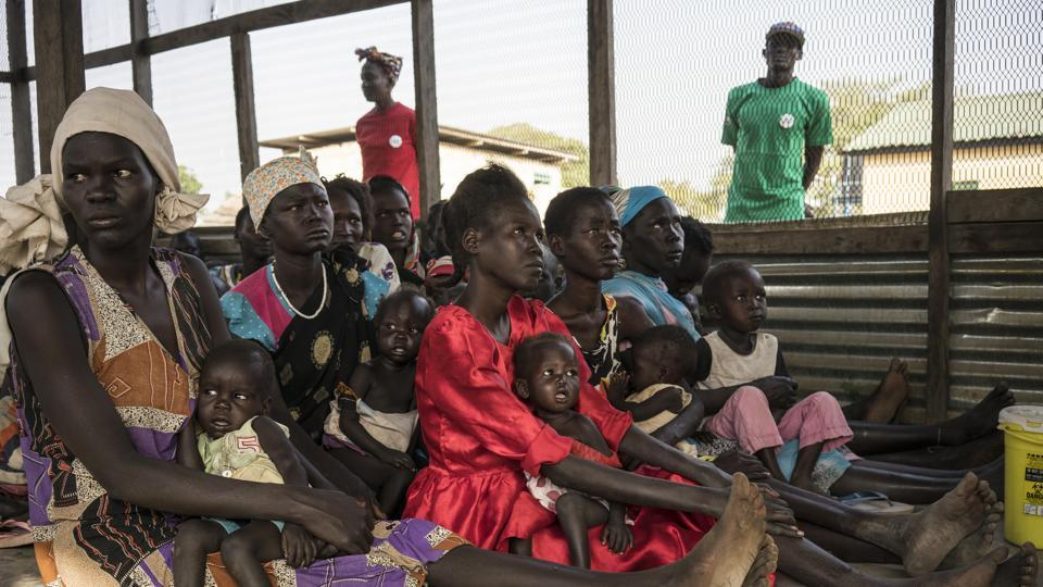 In this photo taken Monday, March 13, 2017, Iman Diing, 20, center, holds her 13-month-old baby daughter Alakaii at a UNICEF-supported outpatient therapeutic program for the malnourished, near Aweil, in South Sudan.