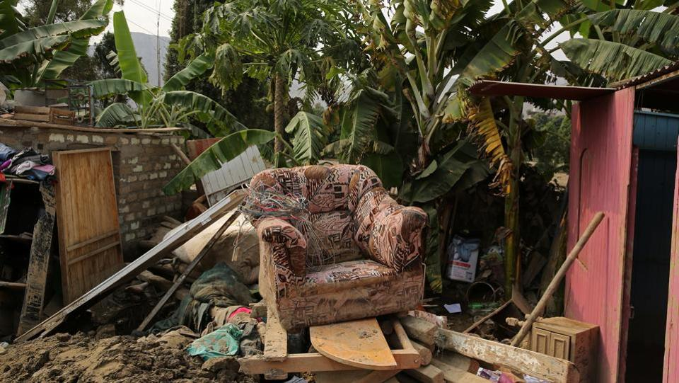 A chair sits on top of belongings after rivers breached their banks due to torrential rains, causing flooding and widespread destruction in Carapongo Huachipa, Lima, Peru. (Mariana Bazo/REUTERS)