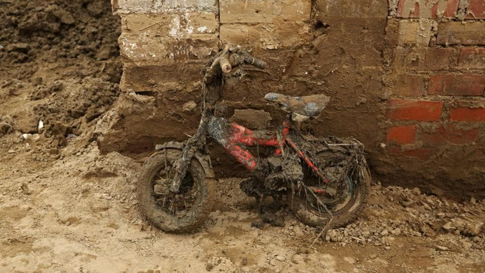 A children's bike leans against a wall covered in mud after rivers breached their banks. (Mariana Bazo/REUTERS)