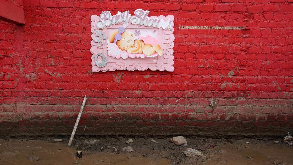 A baby shower sign hands on a wall at the home of Carlos Rojas. (Mariana Bazo/REUTERS)