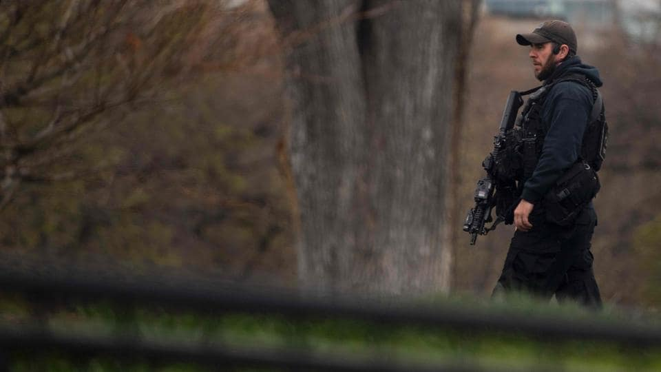 A Secret Service officer patrols the north lawn at the White House in Washington, DC, during a lockdown for a suspicious package near the White House grounds.