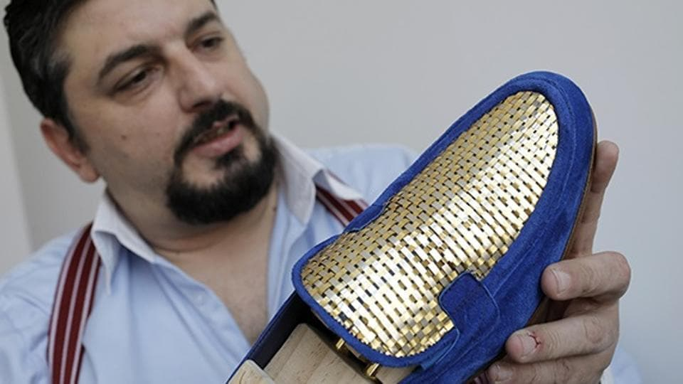 """Antonio Vietri, artisan and founder of A&V Fashion, shows a men's shoe as part of his collection """"Gold""""."""