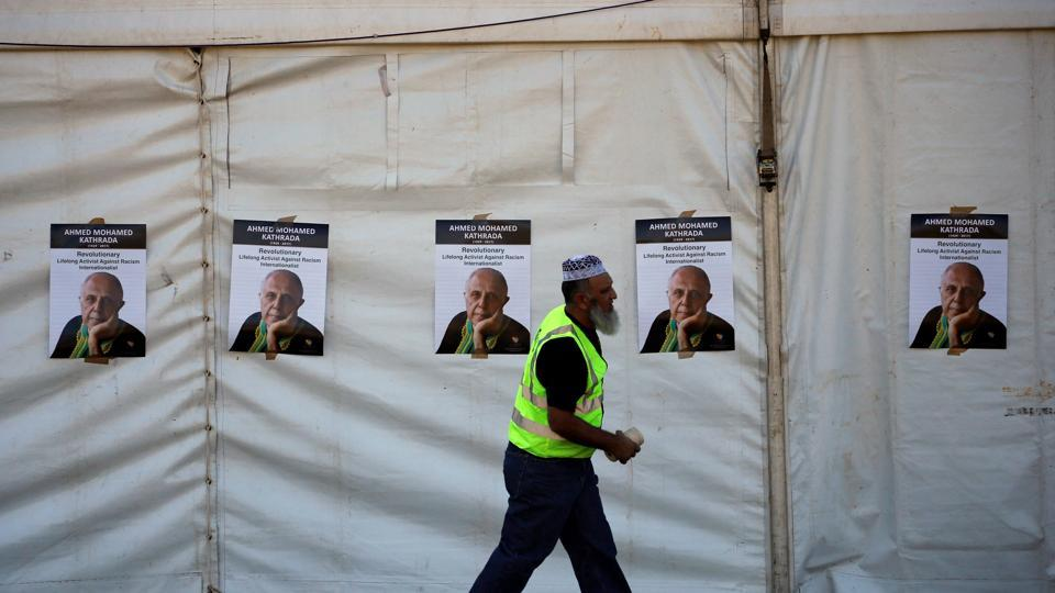 A worker walks past posters bearing the face of Veteran South African anti-apartheid activist Ahmed Kathrada. (Siphiwe Sibeko/REUTERS)
