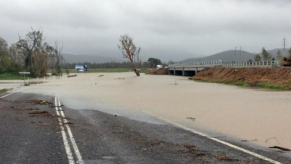 Flood waters submerging part of a highway near the Cyclone Debbie-hit Bowen area in Queensland.  (AFP PHOTO / QUEENSLAND POLICE SERVICE / Handout )